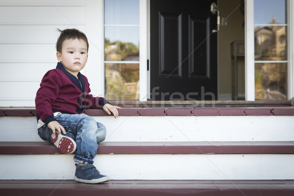 Melancholy Mixed Race Boy Sitting on Front Porch Steps Stock photo © feverpitch