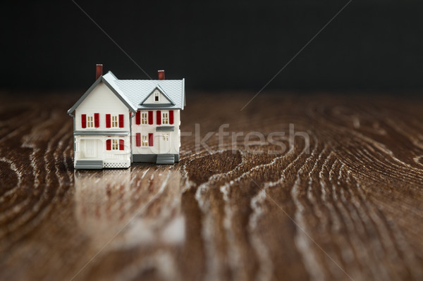 Model Home on Reflective Wooden Surface. Stock photo © feverpitch