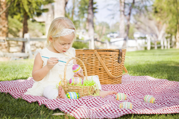 Cute Baby Girl Coloring Easter Eggs on Picnic Blanket Stock photo © feverpitch