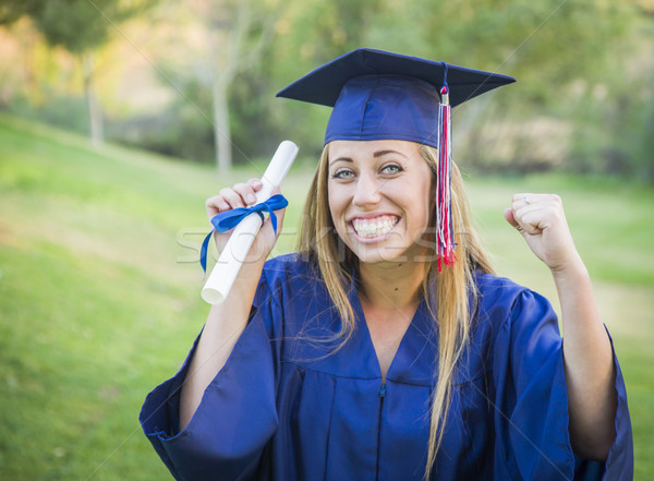Expressive Young Woman Holding Diploma in Cap and Gown Stock photo © feverpitch