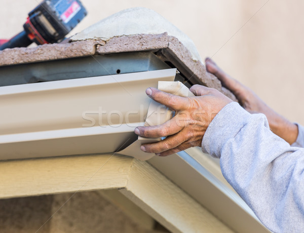 Worker Attaching Aluminum Rain Gutter to Fascia of House. Stock photo © feverpitch