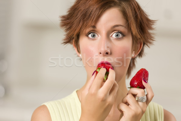 Pretty Wide-eyed Red Haired Woman Biting Strawberry Stock photo © feverpitch