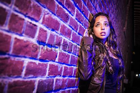 Stock photo: Frightened Pretty Young Woman Against Brick Wall at Night