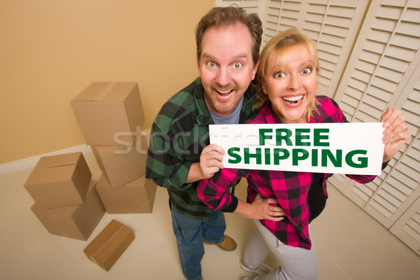 Goofy Couple Holding Free Shipping Sign Surrounded by Boxes Stock photo © feverpitch