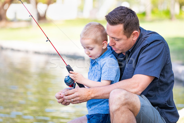 Young Caucasian Father and Son Having Fun Fishing At The Lake Stock photo © feverpitch