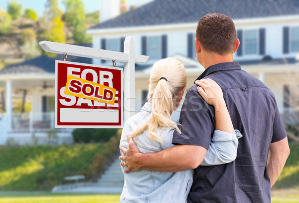 Young Adult Couple Facing Front of Sold Real Estate Sign and Hou Stock photo © feverpitch