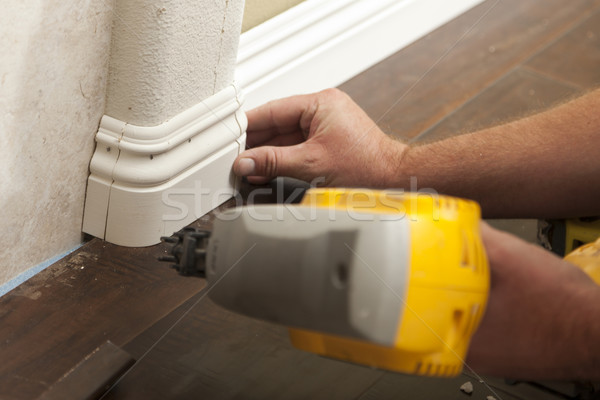 Stock photo: Nailing New Baseboard with Bull Nose Corners and New Laminate Fl