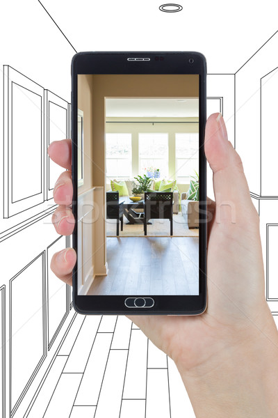 Hand Holding Smart Phone Displaying Photo of House Hallway Drawi Stock photo © feverpitch