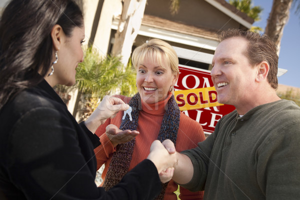 Hispanic Female Real Estate Agent Handing Keys to Excited Couple Stock photo © feverpitch