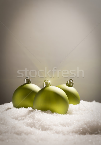 Green Christmas Ornaments on Snow Over a Grey Background Stock photo © feverpitch