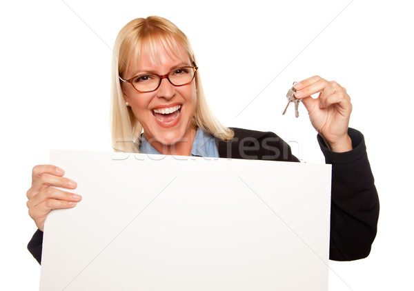 Attractive Blonde Holding Keys and Blank White Sign Stock photo © feverpitch
