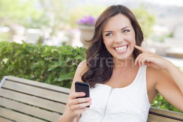 Mosolyog fiatal felnőtt női sms chat mobiltelefon kint Stock fotó © feverpitch