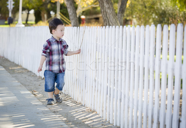 Young Mixed Race Boy Walking with Stick Along White Fence Stock photo © feverpitch