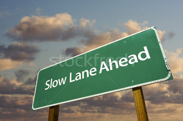 Slow Lane Ahead Green Road Sign Over Clouds Stock photo © feverpitch