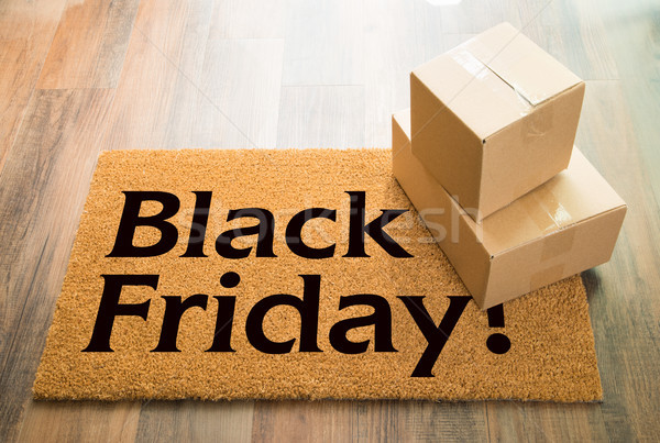 Black Friday Welcome Mat On Wood Floor With Shipment of Boxes Stock photo © feverpitch