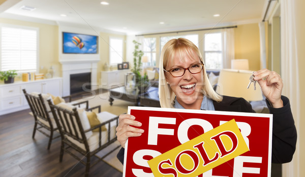 Young Woman Holding Sold Sign and Keys Inside Living Room Stock photo © feverpitch