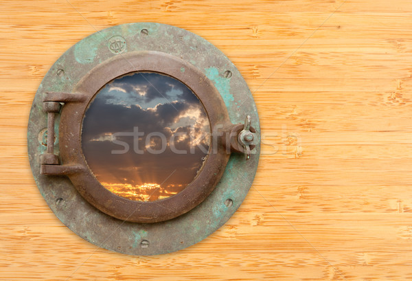 Antique Porthole with View of Sunset on Bamboo Wall Stock photo © feverpitch