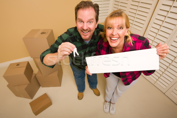 Goofy Couple Holding Keys and Blank Sign Surrounded by Boxes Stock photo © feverpitch