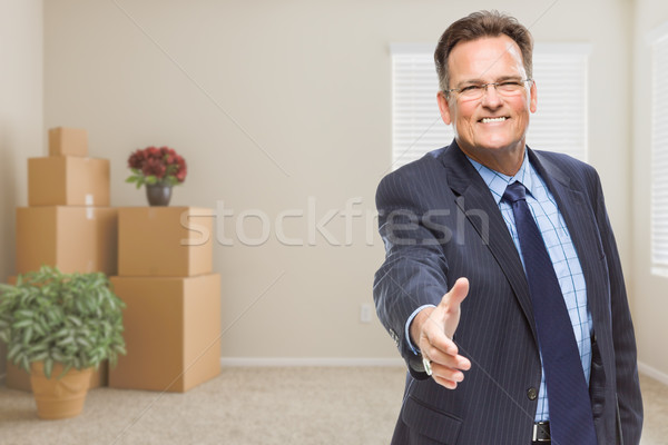 Businessman Reaching for Hand Shake in Room with Packed Boxes Stock photo © feverpitch
