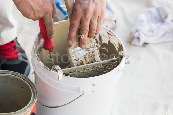 Professional Painter Loading Paint Onto Brush From Bucket Stock photo © feverpitch