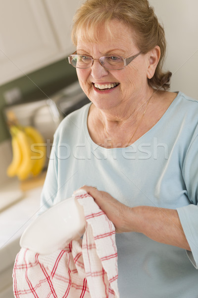 Senior Adult Woman Drying Bowl At Sink in Kitchen Stock photo © feverpitch