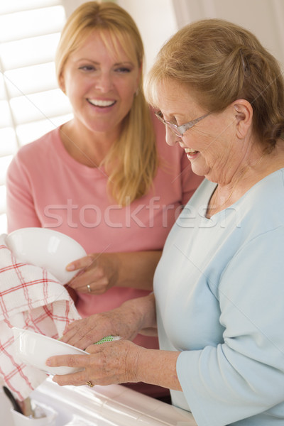 Senior Adult Woman and Young Daughter Talking in Kitchen Stock photo © feverpitch