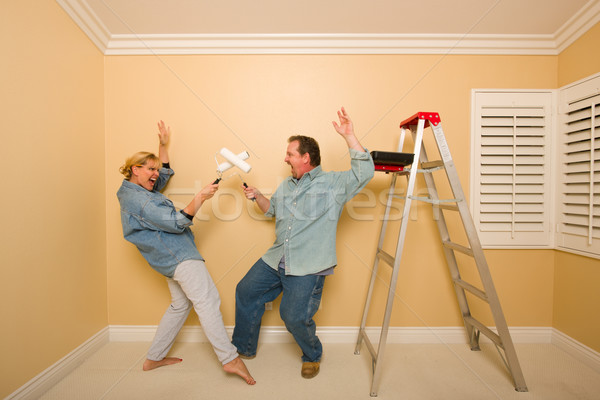 Fun Couple Playing Sword Fight with Paint Rollers Stock photo © feverpitch