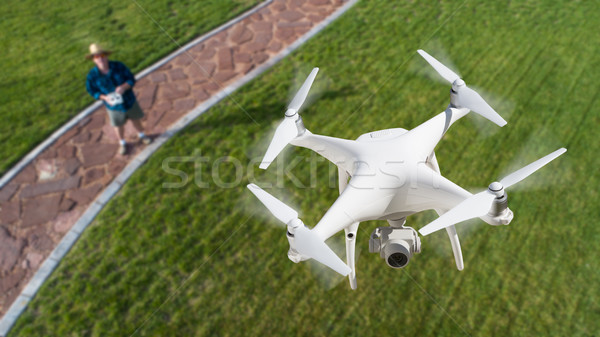 Drone Quadcopter (UAV) In Air Above Pilot With Remote Controller Stock photo © feverpitch