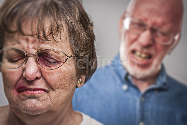 Battered and Scared Woman with Ominous Man Behind Stock photo © feverpitch