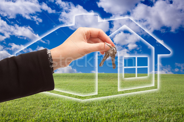 Stock photo: Handing Over Keys on Ghosted Home Icon, Grass Field and Sky