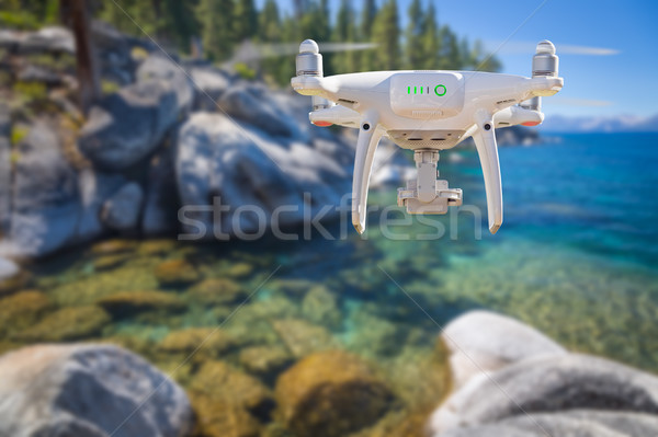 Back of Unmanned Aircraft System (UAV) Quadcopter Drone Flying A Stock photo © feverpitch