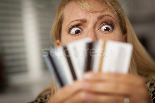 Upset Woman Glaring At Her Many Credit Cards Stock photo © feverpitch