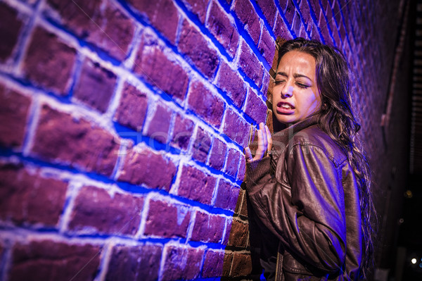 Frightened Pretty Young Woman Against Brick Wall at Night Stock photo © feverpitch