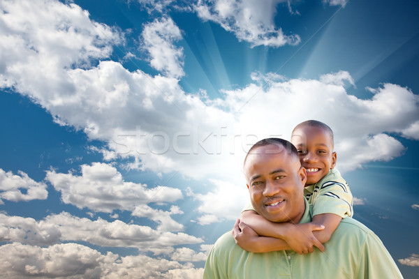 Happy African American Man with Child Over Clouds and Sky Stock photo © feverpitch