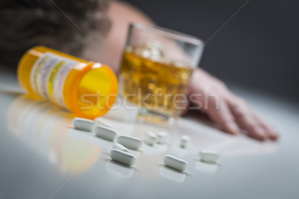 Passed Out Man Behind Scattered Drugs and Glass of Alcohol Stock photo © feverpitch