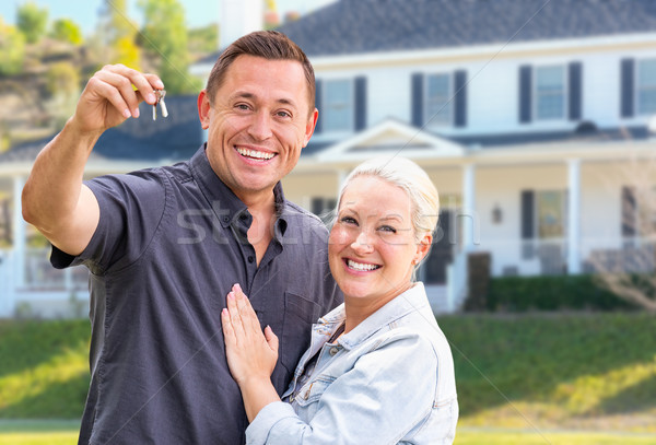 Young Adult Couple With House Keys In Front of Beautiful Home Stock photo © feverpitch