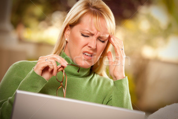 Grimacing Woman Using laptop Suffering a Headache Stock photo © feverpitch