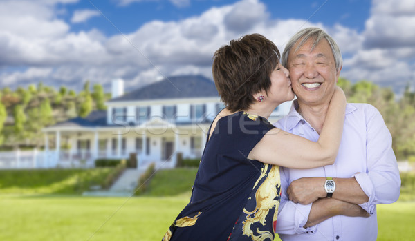 Affectionate Senior Chinese Couple In Front of Beautiful House Stock photo © feverpitch