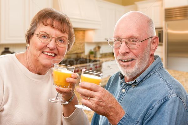 Happy Senior Couple with Glasses of Orange Juice Stock photo © feverpitch