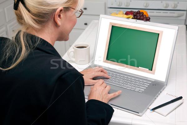 Stock photo: Woman In Kitchen Using Laptop - Chalkbaord