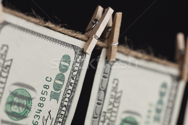 Hundred Dollar Bills Hanging From Clothesline on Dark Background Stock photo © feverpitch