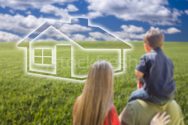 Young Family in Grass Field with Ghosted House in Front Stock photo © feverpitch