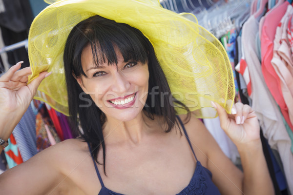 Pretty Italian Woman Trying on Yellow Hat at Market Stock photo © feverpitch