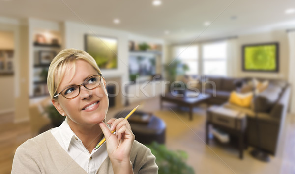 Stock photo: Daydreaming Woman with Pencil Inside Beautiful Living Room