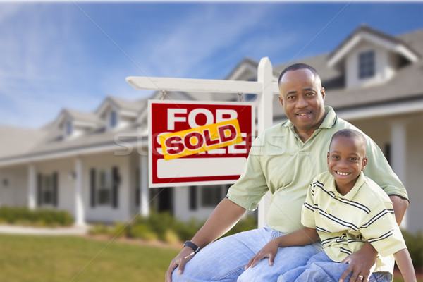 Father and Son In Front of Sold For Sale Sign and House Stock photo © feverpitch