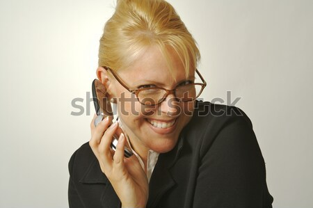 Elated Businesswoman Smiles While Using Her Cell Phone Stock photo © feverpitch