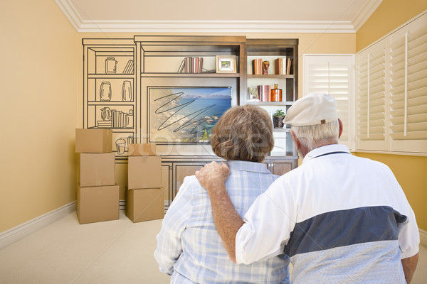 Senior Couple Looking At Drawing of Entertainment Unit In Room Stock photo © feverpitch