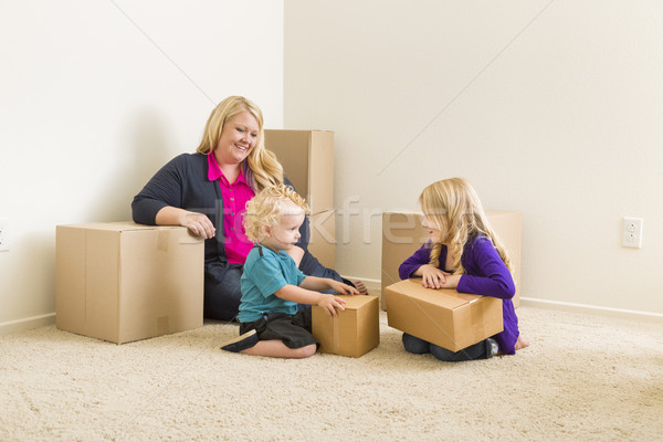 Young Family In Empty Room with Moving Boxes Stock photo © feverpitch