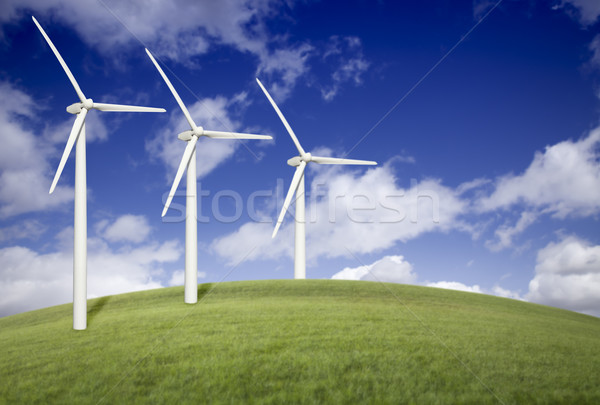 Three Wind Turbines Over Grass Field and Blue Sky Stock photo © feverpitch