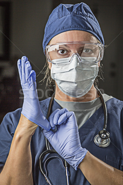 Concerned Female Doctor or Nurse Putting on Protective Facial We Stock photo © feverpitch